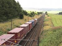 With Carstairs East Junction in the distance, a consignment of ECS Eurocontainers passes below the A70 road bridge on the Edinburgh line on 31 August 2016. The train is the 0422 Tees Dock – Mossend Euroterminal.    <br><br>[John Furnevel&nbsp;31/08/2016]