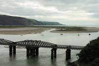 With the Barmouth Viaduct in the foreground, this view looks across the estuary to the Ferry terminus of the Fairbourne Railway on 19th September 2016. A wisp of steam by the building indicates a train has just arrived from Fairbourne. <br><br>[Mark Bartlett&nbsp;19/09/2016]