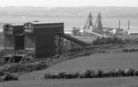 Looking over Hunterston Import Terminal. One bunker was for coal, the other for iron ore. In the background the Midrex direct reduction plants can be seen - never used and later sold, dismantled and reassembled in the United States. (Now said to be in Saudi Arabia). It was to access this that the low level siding was built.<br> <br> An EMU can be seen on the Largs branch.<br><br>[Bill Roberton&nbsp;//1992]