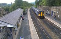 A four-car Sprinter service slows for the Greenfield stop working from Manchester to Huddersfield via the Standedge route on 7th October 2016. Note the curious little waiting room built into the retaining wall on the Eastbound Platform 2.<br><br>[Mark Bartlett&nbsp;07/10/2016]