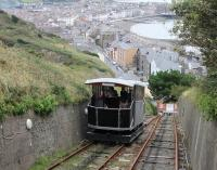 Funicular cars crossing at the mid-point of the Aberystwyth Cliff Railway in September 2016, with the bay and promenade visible behind. The change in gradient for the final stretch down to the lower station is very noticeable. <br><br>[Mark Bartlett&nbsp;18/09/2016]