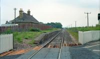 View east at the former Kinloss station in 1990. This station was relocated further east to the junction of the branch to Findhorn on its opening and returned to the original location on closure of the branch. The building dates form the third incarnation. Note the westbound platform on the right, now obscured by foliage.<br><br>[Ewan Crawford&nbsp;//1990]