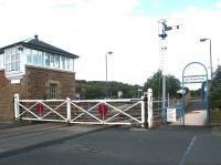The level crossing at Haydon Bridge, Northumberland, in September 2003. At that time the crossing gates were still manually operated using a wheel within the signal box, but have since been replaced by modern lifting barriers. [See image 46308]