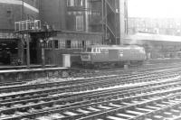 Hymek D7058 standing alongside Paddington Arrival signal box in the 1960s. Occupying the area in the background on both sides of the box is the large Paddington Parcels Depot, complete with its own platform. [See image 41238]