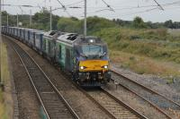 Two nearly new DRS Class 68s, 68020 <I>Reliance</I> and 68018 <I>Vigilant,</I> take the <I>Tesco Express</I> north through Hest Bank on a gloomy 20th August 2016.