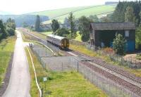 A northbound service from Tweedbank approaching out of the sun hurries past the site of Fountainhall station on 17 August 2016. The train is about to pass over the Network Rail access pad marking the approximate site of the former level crossing (the photograph was taken from the replacement overbridge). The old station building remains boarded up and gradually falling into a state of disrepair [see image 6220].