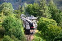 Both ^The Jacobite^ trains pass each other at Glenfinnan. Black 5 No.44871 is hidden by the trees heading back to Fort William, and, sister engine 45407 has just arrived with the afternoon train to Mallaig.