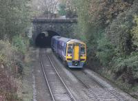 Northern 158797, on a Manchester Victoria to Leeds service, leaves Winterbutlee Tunnel and continues towards the (new) Walsden station on 31st October 2016. Inside the 300yd tunnel, the tail lamp and silhouette of a westbound loaded coal train can be seen as it climbs towards the Summit Tunnel. The train is passing the site of the original station, closed in 1961.<br><br>[Mark Bartlett&nbsp;31/10/2016]
