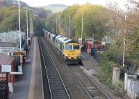 Freightliner 66562 climbs through Walsden with a loaded coal train travelling from Ferrybridge to Fiddlers Ferry on 31st October 2016. The present Walsden station opened in 1990, replacing the original that closed in 1961.<br><br>[Mark Bartlett&nbsp;31/10/2016]