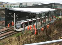 Work on the new tram platform at Edinburgh Gateway stops temporarily following the sound of the warning klaxon on 14 November as a wet tram emerges from under the A8 and passes by on its way to the airport. The new interchage is scheduled to open next month.<br><br>[John Furnevel&nbsp;14/11/2016]