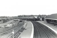 Looking north over the goods yard and west side platforms 1 and 2 at Kilwinning station on Saturday 4 July 1959. In the background an Edinburgh Princes Street - Ayr train is about to call at platform 4. The train is hauled by Dalry Road shed's Black 5 no 44994. <br><br>[G H Robin collection by courtesy of the Mitchell Library, Glasgow&nbsp;04/07/1959]