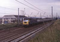 47445 passes the Leyland Trucks factory near Farington Junction with a Blackpool North to Manchester Victoria <I>Club Train</I> in the early 1980s. The siding serving the works was disused for many years but in 2016 became the location for a temporary DMU servicing point during the Blackpool line electrification works. The former D1561 was withdrawn in 1991 and scrapped by Booth Roe in Rotherham three years later. <br><br>[Mark Bartlett&nbsp;//1981]
