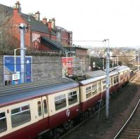 A Motherwell – Dalmuir train calls at Hamilton Central platform 1 on 17 March 2006. Note the building on the upper left with the covered stairway linked to the station's south wall. This is the former entrance and booking office on Kemp Street [see image 9044]. <br><br>[John Furnevel&nbsp;17/03/2006]