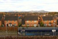 Early morning winter sunshine illuminates the houses of Jenks Loan in the foreground and the Pentland Hills in the background, as a southbound train on the Borders Railway pulls away from the platform at Newtongrange.<br><br>[John Furnevel&nbsp;01/12/2016]