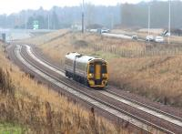 ScotRail 158731 approaching Shawfair from the south on a dismal 15 December 2016 with the 1126 Tweedbank – Edinburgh Waverley. The train has just passed below the Edinburgh City Bypass and is on the double track section between Kings Gate and Newcraighall South. The parallel road traffic is on the rerouted A6106, with Sheriffhall Roundabout in the right background.<br><br>[John Furnevel&nbsp;15/12/2016]