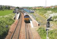 The route is set for down sidings as a Hunterston - Longannet coal train runs slowly through Dunfermline's Queen Margaret station in June 2006 just before entering Halbeath sidings. The train is about to run through the site of Townhill Junction, with the trackbed of the S&D route from Alloa and Stirling on the right. After entering the sidings EWS 66207 will run round its train before heading back to Charlestown Junction where it will take the Kincardine line. [See image 9821] <br><br>[John Furnevel&nbsp;13/06/2006]