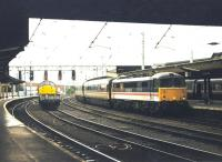 A down WCML service arrives at Carlisle platform 3 in August 1997 behind BR InterCity liveried 87014 <I>Knight of the Thistle</I>, complete with matching set. Held at signals on the centre road is an EWS class 37 with a lightweight freight.<br><br>[John Furnevel&nbsp;/08/1997]