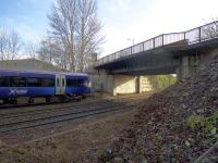 An Alloa - Glasgow Queen Street service about to pass under the A905 Kerse Road overbridge. Plans have been submitted for its replacement as part of the preparation for electrification. The current bridge could accommodate 4 tracks but its replacement will span only the existing 3 tracks.<br><br>[Colin McDonald&nbsp;30/01/2017]