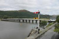 The lower quadrant signals at Penmaenpool are a nice reminder that the hotel access road in the foreground occupies the old GWR trackbed. This view looks east with the old station site just out of sight beyond the bridge toll house. The wooden toll bridge over the Mawddach Estuary still carries road traffic.  <br><br>[Mark Bartlett&nbsp;19/09/2016]