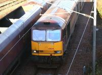 EWS 60029 <I>Clitheroe Castle</I> entering Millerhill Yard from the north in November 2004 with empties returning from STVA Bathgate [see image 18357]. The train is passing a class 66 heading in the opposite direction with coal empties. The line visible top left is the reversing siding used by trains terminating at nearby Newcraighall station.  <br><br>[John Furnevel&nbsp;23/11/2004]