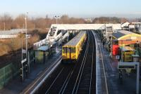 Merseyrail 507006 pulls away from Aintree heading for Ormskirk on 7th February 2017. The bright sunshine has made a large gold horseshoe in the middle of the footbridge almost invisible in this image. The old excursion platforms used by race goers are still partly in place behind the left hand platform.<br><br>[Mark Bartlett&nbsp;07/02/2017]