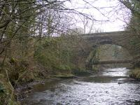 The railway viaduct just south east of Calderpark Halt once loomed high over both the North Calder Water and the still extant road bridge in the photograph. The long demolished viaduct crossed the river at an angle and continued above the left abutment of the road bridge seen here. Apart from a very short section on the west bank of the river where one of the viaduct abutments survives, the solum on both sides of the river crossing has since been landscaped and built over.<br><br>[Colin McDonald&nbsp;15/02/2017]