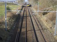 A class 318 EMU on a Dalmuir Whifflet service passes the site of the original Baillieston station. The houses seen top left in the background are on the site of sidings serving Calderbank Colliery which was itself accessed via a short tunnel.  In the right foreground was the signal box and junction for the goods station at Baillieston.<br><br>[Colin McDonald&nbsp;14/03/2017]