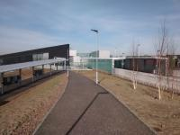 The street approach to seen on 27/03/2017. The tram stop is on the left with the station on the right. A distinct lack of people around, as is my experience of this place so far. Give it time, though ...<br><br>[David Panton&nbsp;27/03/2017]