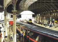 Busy platform scene at Newcastle Central in April 1997, with a GNER Kings Cross - Edinburgh train boarding at platform 2, as the up <I>Highland Chieftain</I> runs into platform 3. A Pacer stands at bay platform 1 in the left background.<br><br>[John Furnevel&nbsp;05/04/1997]