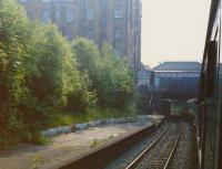 A view to the rear of a diverted Birmingham train passing under the footbridge at Morningside Road station in July 1989. Another passenger train is just visible disappearing under Morningside Road  OB11 as a bus passes over it.<br><br>[Charlie Niven&nbsp;/07/1989]