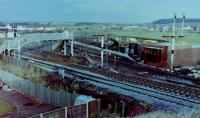 Looking northeast from the road bridge over Barassie Junction, Monday, 29 November, 1982, with the weekend's work by the PW and signalling engineers plain to see (well it would be if the photo was of better quality). Track-wise, the Kilmarnock line had been reduced to a single line (until that weekend, double track had extended round the curve onto the straight towards Drybridge before converged into single line to Kilmarnock, whilst a new crossover had been formed from the slewed 'up' (southbound) main line onto the old alignment of the same line, both 'Up' and 'Down' main lines slewed west starting from the platform ends approximately. The semaphore signals were in the process of being felled, their arms already removed, their replacements in the form of colour lights just about visible beyond the footbridges (that over the Kilmarnock lines was removed along with the signals, whilst the other section over the line to Irvine survived until electrification saw it replaced, circa 1985. The temporary Signalbox, officially opened that day, is the brick-built structure on the east side of the line between the footbridge and the remains of the Kilmarnock line bracket signal. <br><br>[Robert Blane&nbsp;29/10/1982]