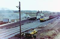 Unidentified Class 47 diesel photographed heading north with a freight train on the newly opened (that morning) junction deviation at Barassie, Monday, 29 November, 1982, the redundant Signalbox (officially closed the day before) already being demolished and its funeral pyre emitting plenty of smoke. The old 'Down' (to Irvine) line behind the Signalbox was later lifted but the 'Up' line was retained, the Kilmarnock line running into this line (with facing connection off the re-aligned main line at the south end of Barassie station platforms), the route south onto the Troon avoiding line became the run-round loop in Barassie Yard, and the old alignment onto the Troon Loop and Troon station became the 'up' loop.<br><br>[Robert Blane&nbsp;29/11/1982]