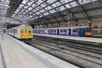 Two <I>Northern Electrics</I> sit in the north side platforms at Lime Street station on 6th April 2017. 319450, newly arrived from Preston, is as yet unbranded but 319382, waiting on the right to depart to Warrington, has full Northern livery. <br><br>[Mark Bartlett&nbsp;06/04/2017]