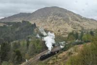 In light rain, a Jacobite service, returning from Mallaig, leaves Glenfinnan. The view is from <i>The Viaduct Trail</i>, a relatively easy path (think West Highland Way) from the station to above the west end of Glenfinnan Viaduct. <br><br>[Ewan Crawford&nbsp;27/04/2017]