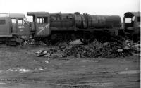 45699 <I>Galatea</I> looking very woebegone in Barry scrapyard in 1975. Compared with Bill Jamieson's picture five years earlier the centre driving wheels have been cut through and the chimney has disappeared. The loco left the yard in 1980 to Tyseley, originally as a source of spares, but in 2002 went to West Coast Railways - and the rest is preservation history [See image 47860]. The NBL Type 2 buffered up to 45699 is widely reported as D6122, but one cab displayed D6121 as seen here leading to disputes about identity. <br><br>[Mark Bartlett&nbsp;28/10/1975]