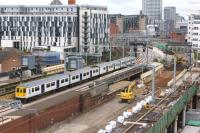 A Liverpool to Manchester Victoria stopping service passes Salford Central on the newly re-aligned track through what may become platform 3. Until a few weeks ago these lines between Ordsall Jct and Deal St Jct ran to the right where the digger is located.<br><br>[John McIntyre&nbsp;19/05/2017]