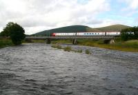 A dark and dangerous looking River Clyde at Lamington, photographed during the early evening on 1 September 2006. In the background a Virgin Voyager crosses the viaduct southbound, heading for Birmingham New Street.<br><br>[John Furnevel&nbsp;01/09/2006]