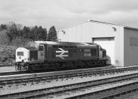 EE Type 3 37418, stranded by the Ness Viaduct collapse, sits outside the temporary Muir of Ord shed in 1990. After a long mainline career this loco went into preservation on the East Lancashire Railway.<br> <br><br>[Bill Roberton&nbsp;//1990]
