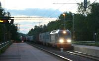 Dusk is finally approaching as the 22.32 Upptåget leaves Vattholma Station <I> en route </I> for Gävle. It crosses a Down (southbound) container train hauled by a 1996 vintage Hectorrail Class 141 loco with all headlights blazing. For more information on this see <br> http://www.hectorrail.com/products/class-141-queen-of-traction/<br> <br><br>[Charlie Niven&nbsp;13/06/2012]