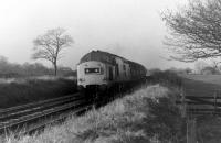 37140 and a rake of tank wagons climb eastwards on Hoghton bank on 1st December 1978. The tanks will probably be empties from Preston Dock or Burn Naze returning to Immingham. 37140 had a further twenty years main line service but was stored in June 1999 and cut up two years later at Springs Branch.  <br><br>[Mark Bartlett&nbsp;01/12/1978]