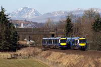 Dunblane-Edinburgh (170 410) and Glasgow-Alloa (170 474) services pass each other near the site of Polmaise Junction on 25th March 2017. The snowy peak of Uamh Bheag looms in the background. <br><br>[Mark Dufton&nbsp;25/03/2017]