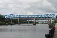 A 4-car Metro unit heads south over the Queen Elizabeth II bridge crossing the Tyne on 26th June 2017. The slight arc of the cantilevered Metro bridge allows a glimpse of a Virgin ECML train on the King Edward VII bridge behind. The bright blue paintwork of the bridge recreates the colour of the old Redheugh road bridge, replaced in the 1980s by a modern concrete structure, the pillars of which can be seen beyond the rail bridge. <br><br>[Mark Bartlett&nbsp;26/06/2017]