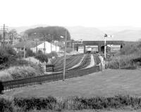 Looking north east  towards Millom station on the Cumbrian Coast line in October 1983 just as a Carlisle – Barrow DMU pulls into platform 1 on the other side of St George's Road bridge. Several sidings still in existence around the station at this time had been associated with the former Millom Ironworks, which closed in 1968 [see image 26680]. <br><br>[John Furnevel&nbsp;07/10/1983]
