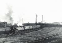 Sunlit Fairburn tank 42243 with a Glasgow bound train at Ardrossan North on 5 July 1959. The Shell refinery stands in the right background. The line to the right formerly served the engine shed.<br><br>[G H Robin collection by courtesy of the Mitchell Library, Glasgow&nbsp;05/07/1959]