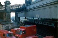 Looking east over the Royal Mail yard alongside Calton Road in 1985 as a southbound train prepares to leave platform 1. The Royal Mail depot at Waverley occupies the north east corner of the station just off to the right. Note the closed pedestrian footbridge which once linked Calton Road and Jeffrey Street [see image 9634].   <br><br>[John Furnevel&nbsp;21/05/1985]
