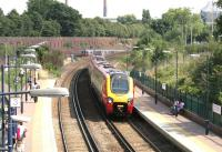 The 14.22 Brighton - Birmingham - Manchester Piccadilly Virgin CrossCountry service runs through platform 4 on the WLL side of West Brompton station in July 2005 as a District Line train on its way up the hill from Fulham Broadway approaches the adjacent London Underground platforms. The Voyager will call at Kensington Olympia on its way across west London. <br><br>[John Furnevel&nbsp;22/07/2005]