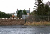 Site of Pomathorn level crossing - looking back towards the old station in December 2005 with the crossing gates now replaced by a wire mesh fence. The sizeable goods yard stood beyond the station house. Pomathorn Mill dominates the left background.<br><br>[John Furnevel&nbsp;11/12/2005]