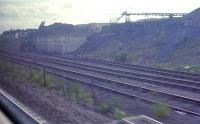 A view of the roughcastle opencast loading pad, near Falkirk, seen from a passing eastbound train in June 1989. In 2011 this remains in place, but overgrown.<br><br>[Ewan Crawford&nbsp;12/06/1989]