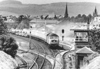 The Perth - Kensington Olympia Motorail service starts to pick up after passing through Dumfries station in April 1971 and is about to run past Dumfries South box. View is north west towards the town centre, with the distinctive outline of St Mary's parish church on the extreme right of the picture.<br><br>[John Furnevel&nbsp;08/04/1971]