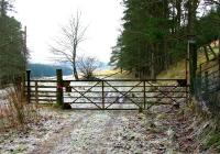 Original gate at the entrance to the railhead at Victoria Lodge in February 2006, looking north along the trackbed. The wooden railings to the left have replaced the former metal pedestrian gate although the original gatepost remains.<br><br>[John Furnevel&nbsp;01/02/2006]